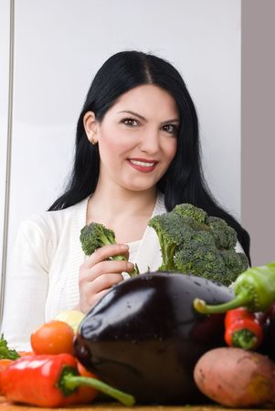 Woman in kitchen with many fresh vegetables holding broccoli and smiling Stock Photo - 4441053