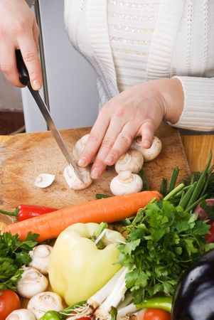 garden stuff: Woman in kitchen slicing  mushroom on wood board and variety of fresh vegetables Stock Photo