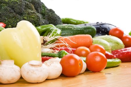 Close up of fresh vegetables on a wood table in kitchen photo