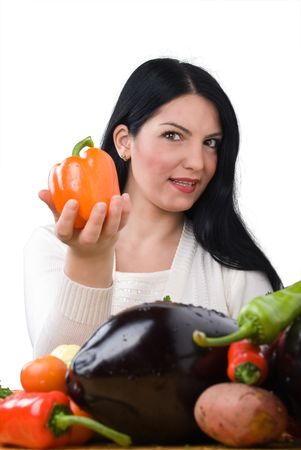 Young woman with fresh vegetables in front of her  giving you a orange capsicum  photo