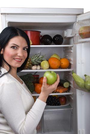 conservacion alimentos: Mujer joven de tomar una manzana verde de su nevera llena de frutas y hortalizas frescas Foto de archivo