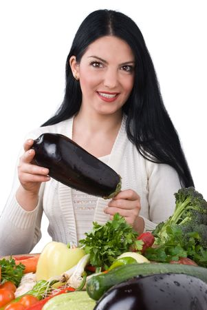 Smiling beautiful woman holding a eggplant in her hands surrounded with fresh vegetables photo