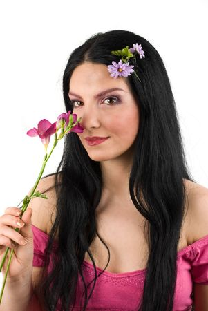 Beautiful young woman smelling a spring flower and looking at you photo