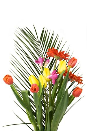 Spring flowers bouquet on a palm leaf isolated on white background photo