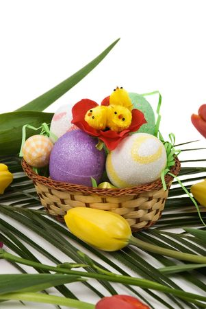 Easter decoration with eggs and chicken in a basket and tulips red and yellow on a palm leaf photo