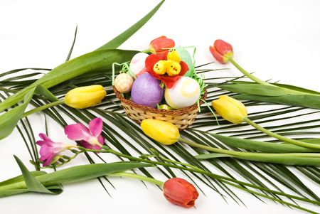 Basket with Easter eggs and chicken on a palm leaf with tulips and spring flower photo