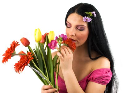 Beautiful young woman with long hair and pink make up smelling spring flowers and enjoying their scent Stock Photo - 4523372
