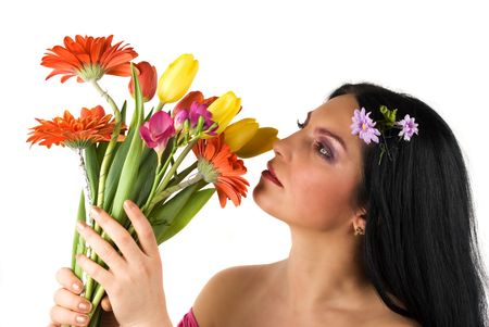 Beautiful profile of a young woman holding up in her hands a bouquet of spring flower and admire or smell them photo