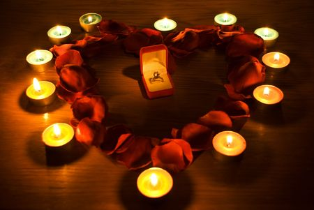 burning love: Diamond ring in a box in the middle of a heart with petals  roses and candles lights  Stock Photo