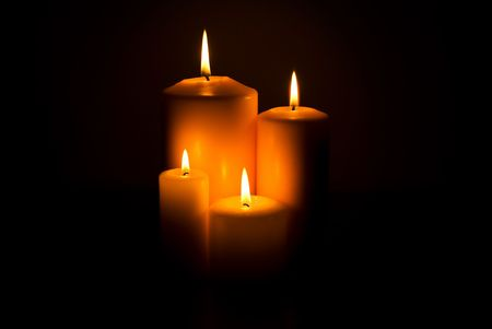 Group of four candles lights in the middle on photo in darkness Stock Photo - 4573629