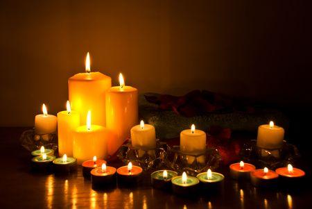 Acuerdo de spa con luces de velas, toallas y pétalos en la oscuridad sobre tabla de madera Foto de archivo