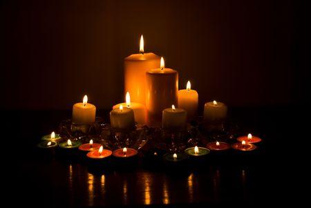 Variedad de luces de las velas con la reflexión sobre una mesa de madera en la oscuridad