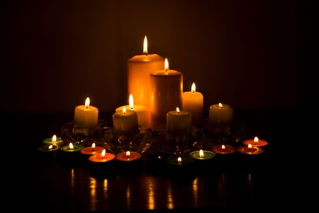 candles spa: Variety of candles lights with reflection on a wood table in darkness Stock Photo