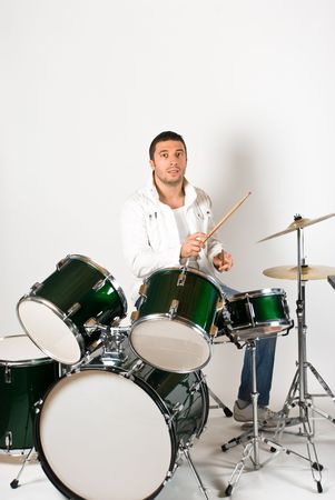 drum set: Active drummer playing at drums set in a studio