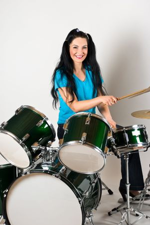Beautiful smiling drummer woman playing and have fun with drums set photo