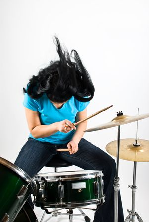 Drummer woman flipping hair feeling the music and play drum kit photo