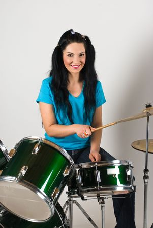 Young woman drummer  playing music on drum set  photo