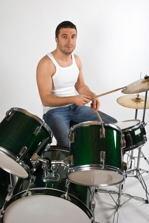 Young attractive man drummer playing drums  and cymbals studio shot photo