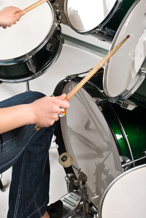 bass drum: Part of woman  legs on drum pedal  holding drumsticks