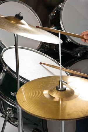 Human hand holding drumsticks playing drums and cymbal