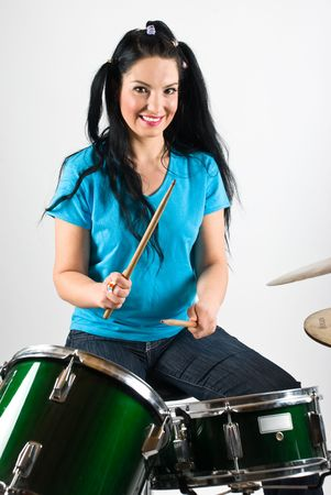 drumming: Beauty drummer with pigtails smiling and playing drum set with drumsticks Stock Photo