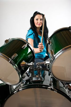 Young  attractive woman holding drumstick and playing drums photo
