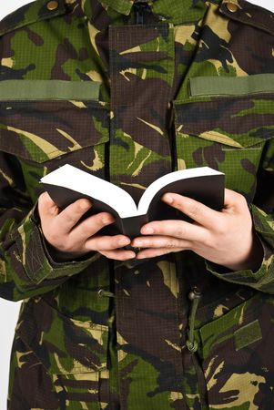 Close up on part body of army soldier  reading a bible  photo
