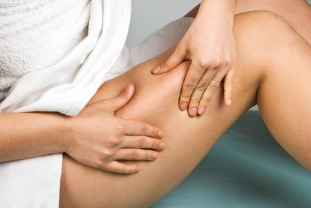 Woman checking cellulite on her legs sitting on massage table