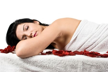 retreat: Woman lying on massage table  with eyes closed at spa retreat seen from profile isolated on white background