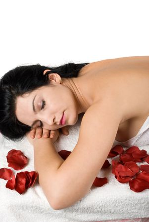 Close up of woman lying on massage table at spa resort with red rose petals around her isolated on white background photo