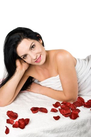 Smile beauty woman at spa resort on massage table  with rose petals isolated on white background photo