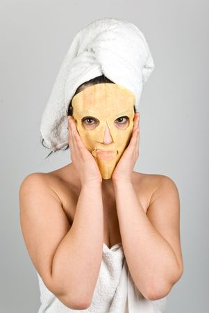 Woman standing and hold with her hands a nutritious  mask for skin problems on her face  photo