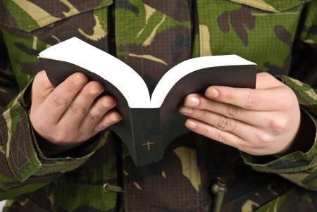 Army soldier reading bible ,selective focus on book and hands photo
