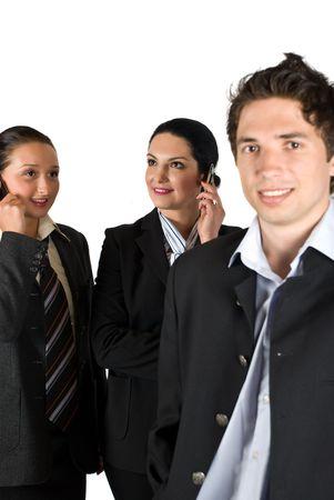 Un grupo de tres personas con dos felices de negocios hablando por tel�fono m�vil en el fondo, se centran en ellos y sonriente hombre de negocios en la esquina frontal derecha de la foto Foto de archivo - 4781167