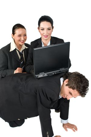 simulate: Business man sitting in a funny position all fours simulate  a desk and two business woman using laptop on his back because do  not have an office