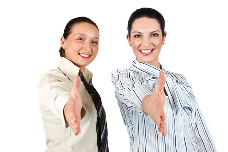 Two beautiful and smiling business women standing with hands open and giving handshake isolated on white background Stock Photo - 4822289