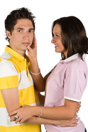 Young couple standing closer one to each other and the woman looking at him  touching his face with hand photo