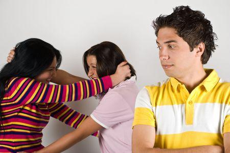argument: Twee jaloerse vrouw vechten voor een jongen terwijl hij kijken met de ogen, op wedstrijd en kijken verbaasd en geamuseerd over situationt, focus op hem Stockfoto