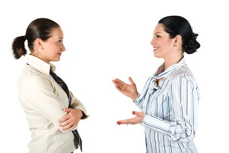 talk to the hand: Two cheerful businesswoman have a conversation,the brunette woman explaining something and gesturing with hands while the other listen her very attentive Stock Photo