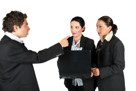 Mad boss screaming at his employeers while the two  woman holding and using a laptop and looking very surprised and shocked at him photo