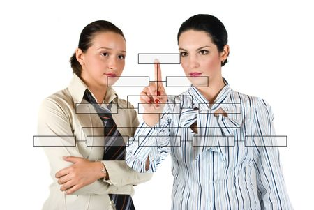 Two business woman  with a blank diagram buttons discussing and one of them pointing on last button Stock Photo - 4850859