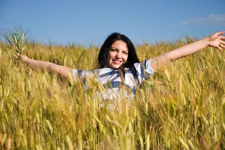 Beautiful young woman enjoying a morning day of  summer   in a yellow field of wheat and sitting on a chair with open hands   photo