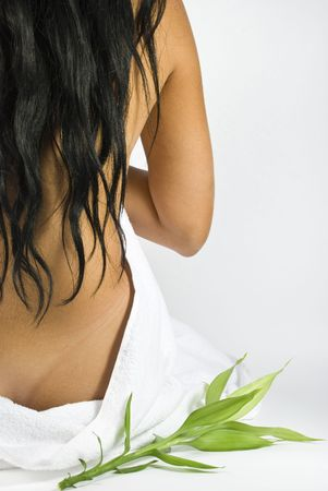 Nude back of woman at spa center massage with bamboo photo