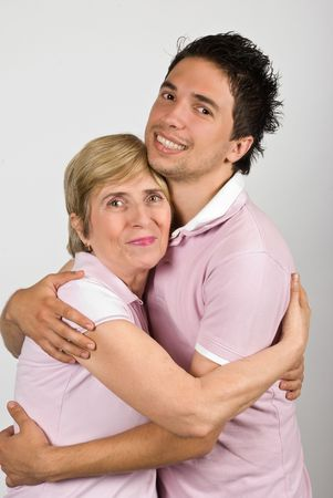 Portrait of mother and adult  son hugging and smiling together and wearing pink tshirts,they are really family,over gray background Stock Photo