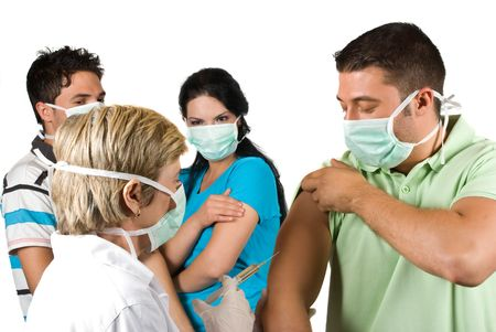 ilness: Mature woman doctor vaccinate a young guy in front of image and other waiting or did the vaccine in background,all people wearing protective mask concept of protect from ilness by vaccination or immunization