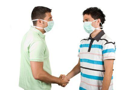 manos estrechadas: Retrato de dos j�venes colegas que apret�n de manos y uso de m�scara protectora concepto de protecci�n contra la gripe