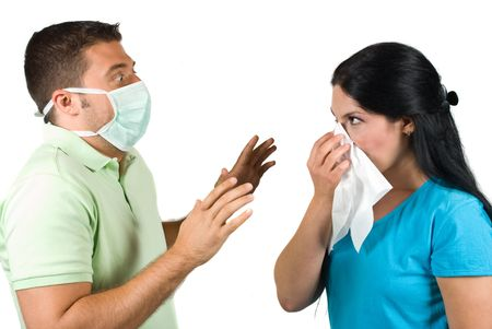 Two people couple in a situation :woman sneeze in a white napkin while the man wearing a protective mask and it is very scared trying to stop her sneezing with his hands,concept of protection from swine flu or other diseases photo