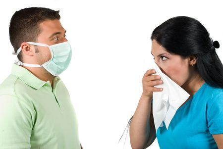 Sick woman having flu and sneeze in a white napkin and the man are terrified,wearing a protective mask  and making big eyes  when she sneezing isolated on white background photo