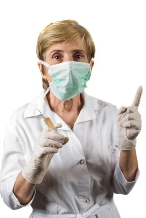 Mature woman  doctor wearing protective mask , holding a syringe  and pointing upwards to copy space isolated on white background photo