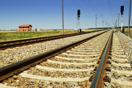 Rails of  train in a sunny day ,house and lanscape in background  photo